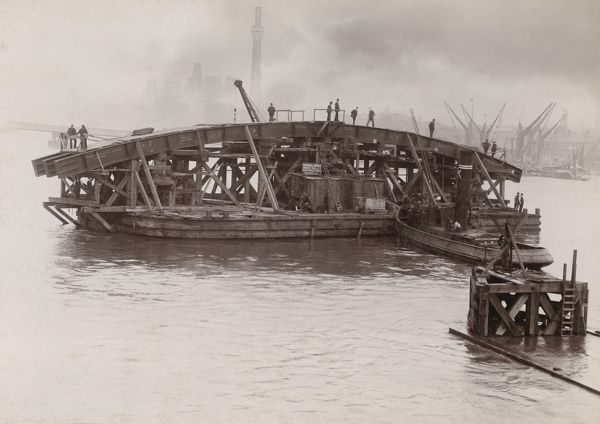 Barges manoeuvring one of the steel arches which would form the new Vauxhall Bridge into place on the River Thames, London. The new Vauxhall Bridge was opened on 26th May 1906, and replaced an earlier bridge constructed in 1811-1816. Photographed by Emberson