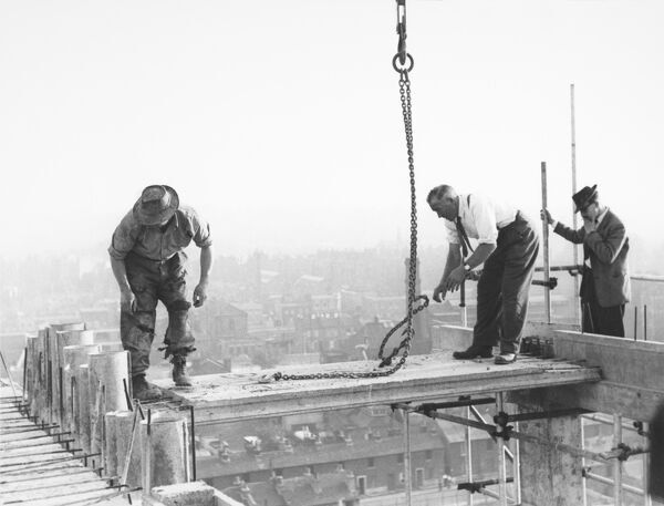 Picton Street, Camberwell, Southwark, London. Two men placing the first precast roof slab of the end bag on top of an eleven-storey block of flats with the Resident Engineer supervising operations. Photographed in October 1955. John Laing Collection