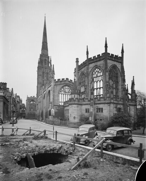Cathedral Church Of St Michael, Bailey Lane, Coventry. The shell of the old Cathedral viewed from the south east with a basement exposed beneath derelict ground at the corner of Bailey Lane and Priory Street. Motor cars are parked on the street