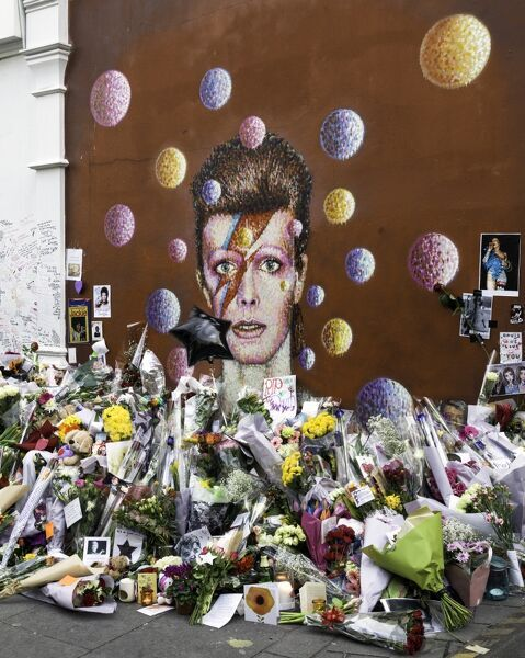 Flowers and tributes surround the mural of musician David Bowie, January 2016. The mural was painted by Australian street artist James Cochran (aka JimmyC) in 2013. Tunstall Road, Brixton, Lambeth, Greater London