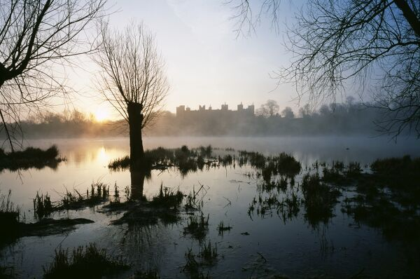 FRAMLINGHAM CASTLE, Suffolk. View looking east across the mere at sunrise with the castle seen through mist