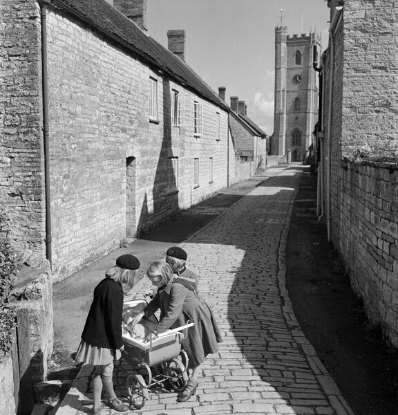 Church Path, Queen Camel, Somerset. Looking along a cobbled street towards the tower of St Barnabas' Church, with three young girls tending to a doll in a pram. Photographed by John Gay in April 1953