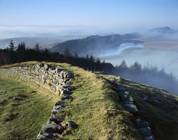 HADRIAN'S WALL, Northumberland. Hotbank Crags, near turret 37B. View from atop the wall out across the mist enshrouded Crag Lough beneath Highshields Crags. hadrian