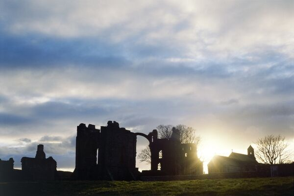 LINDISFARNE PRIORY, Holy Island, Northumberland. View of the priory at sunset