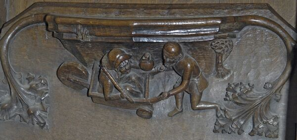Ripon Minster, Minster Close, Ripon, North Yorkshire. Detail view of a misericord in the choirstalls showing carved leaf decoration and figures of a man pushing a woman in a wheelbarrow