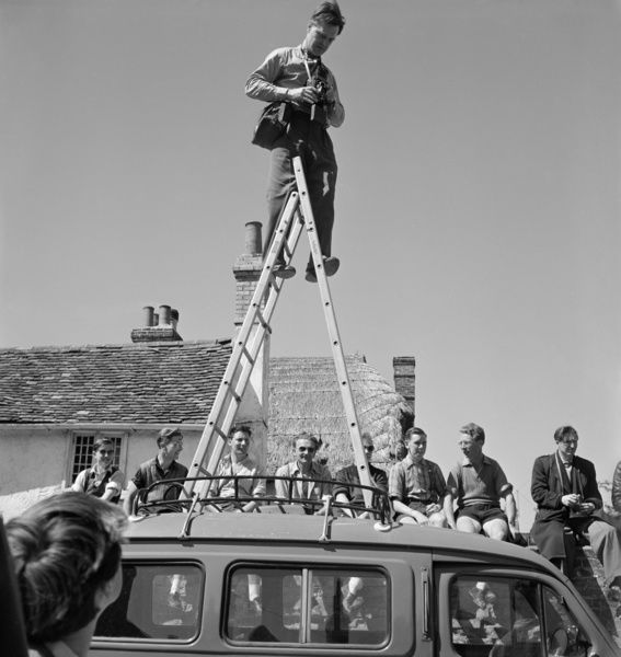 Thaxted, Essex. The photographer John Gay standing on a step ladder mounted on the roof of a van, with a group of men sitting on the wall behind. Photographed by Marie Gay during a Thaxted Morris dancing event, late 1950s