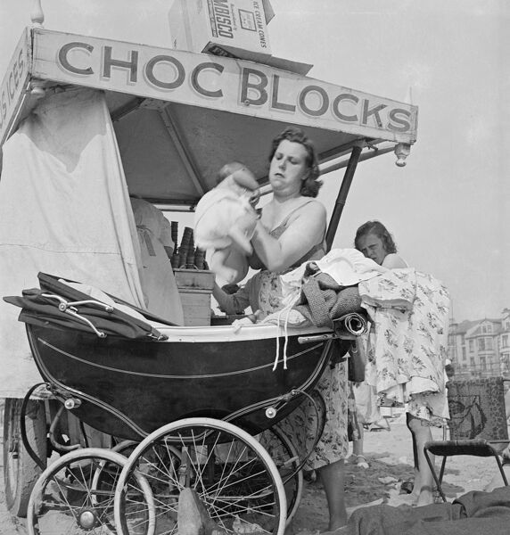 Blackpool, Lancashire. A young mother with baby and pram standing beside an ice cream cart. Photographed by John Gay 1946-55