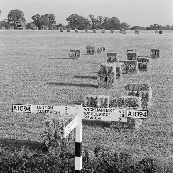 Snape, Suffolk. Signpost and a field of straw bales, on the A1094. Photographed by John Gay in 1962