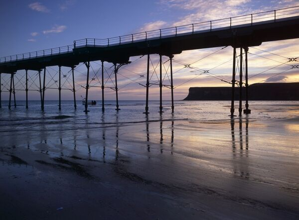 SALTBURN PIER, Saltburn by the Sea, North Yorkshire. Dawn view of the beach, sea and Huntcliffe headland. Start of the Heritage Coast