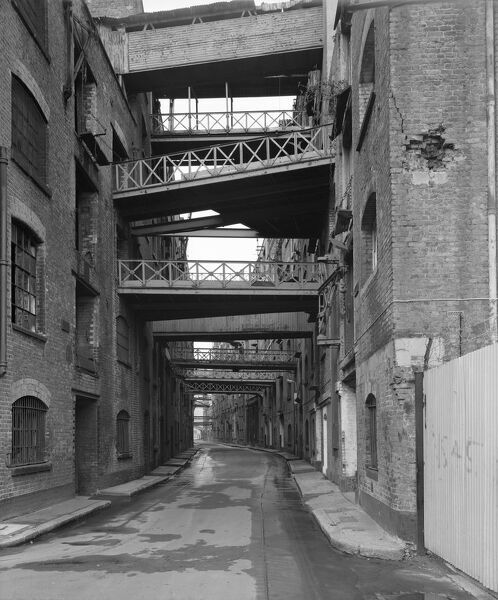 A view looking west along Shad Thames showing The Cardamom Building in the left foreground and the arch carrying Tower Bridge Road across Shad Thames just visible in the distance. Photographed by Paul Barkshire, 19th March 1983