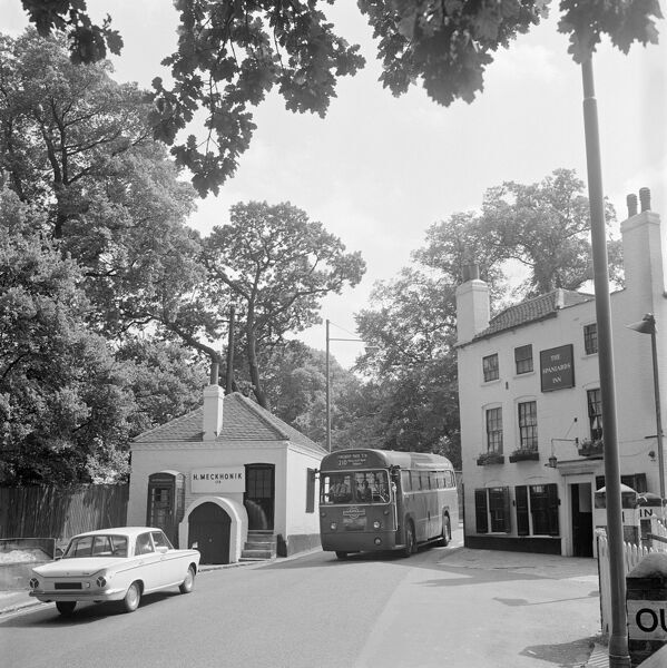 SPANIARDS INN, Hampstead Heath, Hendon, London. The No. 210 bus driving through the narrow gap between the Spaniard's Inn and the old Toll House at the junction of Spaniard's Road and Hampstead Lane, a car waiting for it to pass. Photographer John Gay