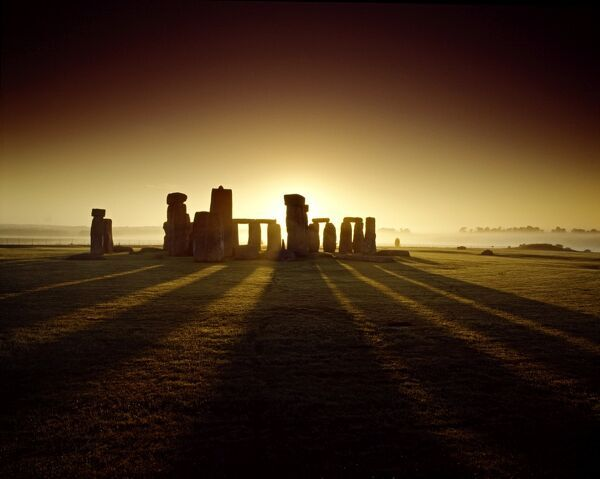 STONEHENGE, Wiltshire. View of the circle from the west at sunrise