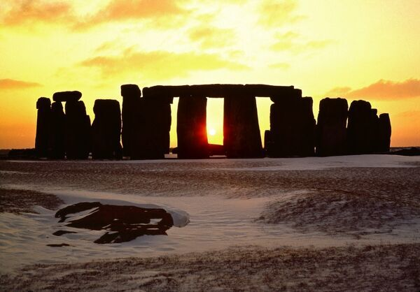 STONEHENGE, Wiltshire. View of the stone circle looking south west along axis. Mid-winter sunset with snow