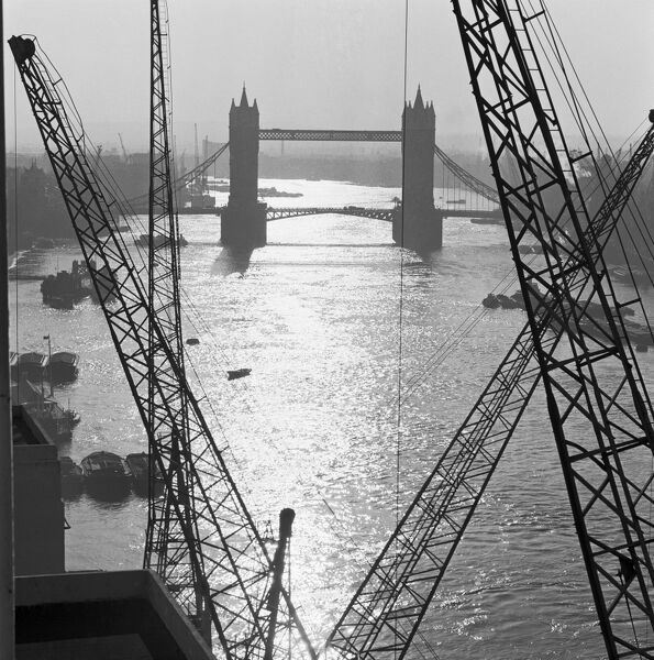 TOWER BRIDGE, London. The bridge seen from riverside gantries, looking east. The Thames is still a major port, with Thames barges and other vessels moored in mid stream. (Reproduced in John Gay, 1964, London Observed). Photographed by John Gay