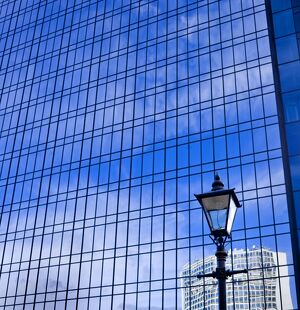 Blue sky reflected in glass tower block DP069226