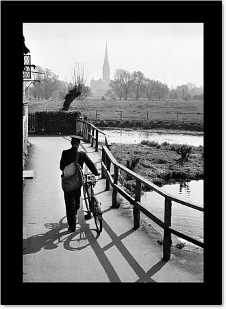 HARNHAM, Salisbury, Wiltshire. View from the Old Mill at Harnham, looking across the water meadows towards Salisbury Cathedral with a postman pushing his bicycle along the Town Path in the foreground. Photographed by John Gay during 1950s - 1960s
