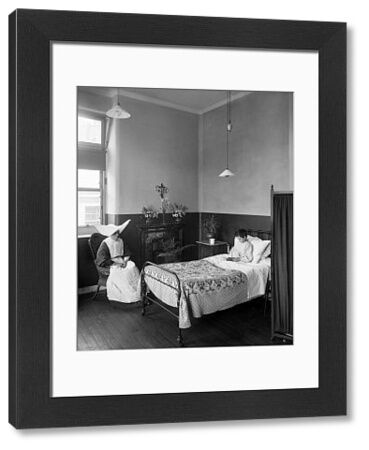 ITALIAN HOSPITAL, Holborn, London. Interior view of a ward at the Italian Hospital with a young boy resting in his bed and a nurse in a distinctive uniform
