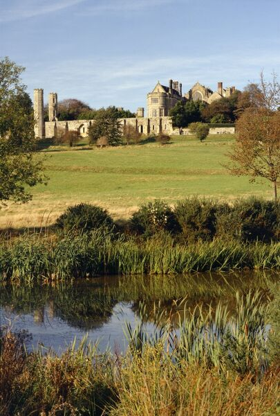 BATTLE ABBEY, East Sussex. View looking across the pond and battlefield towards the abbey