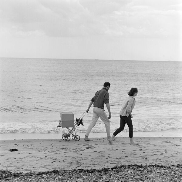 Suffolk. A couple walking along a beach, the man pulling a pram behind him. Photographed by John Gay in 1963