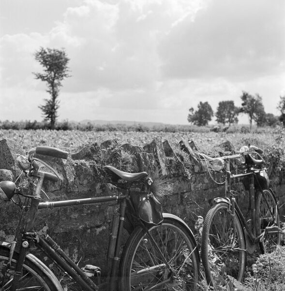 Two bicycles propped against a stone wall in Somerset. Photographed by John Gay during the 1950s