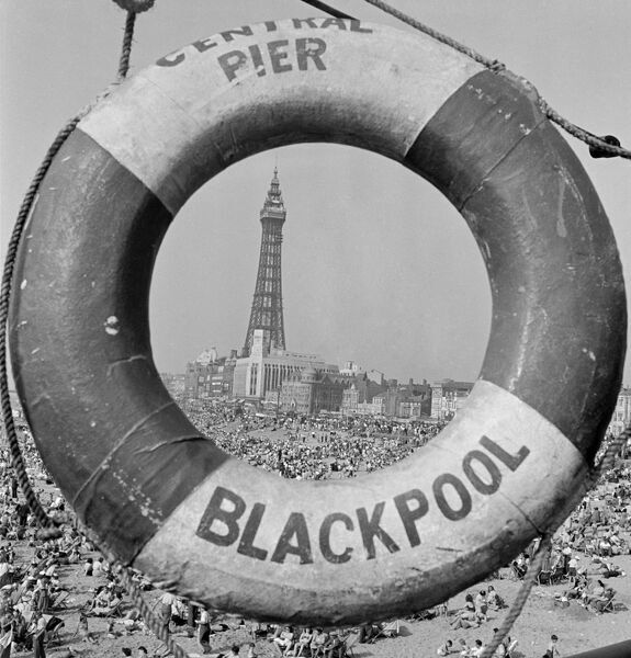 BLACKPOOL, Lancashire. General view along beach towards the Blackpool Tower seen through centre of ring of life buoy on central pier. Mid 20th century. John Gay
