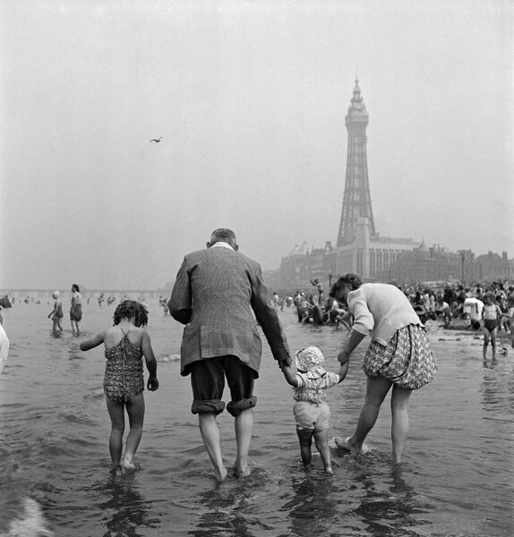 BLACKPOOL, Lancashire. Informal holiday portrait showing rear view of a family with two small daughters paddling in the sea, with Blackpool Tower in the background (mid-20th century). John Gay