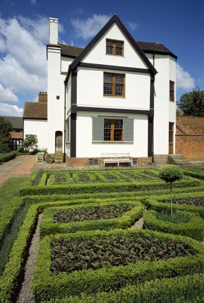 BOSCOBEL HOUSE, Staffordshire. View from the south with garden laid out in small formal beds edged with box and benches by the house