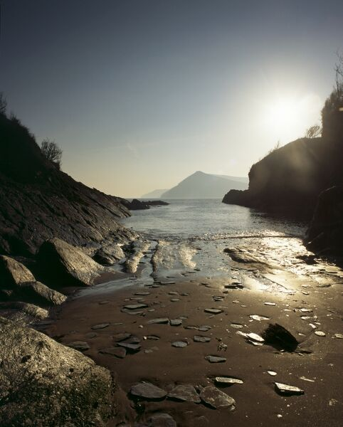 BRIERY HARBOUR, west of Combe Martin, Devon. A view of the sandy cove lit by sunlight