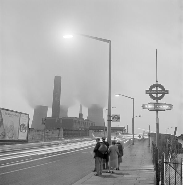 HARLESDEN, London. A street scene with people waiting at a bus stop by a London Underground station sign in Harlesden at dusk, cars passing and the North Acton power station to the south of Harlesden Station in the background