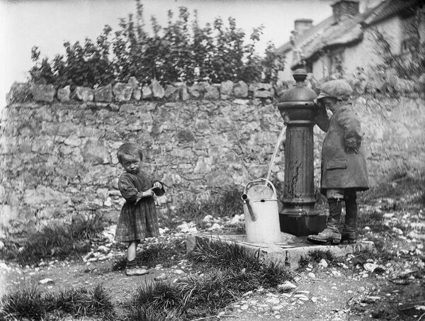 Two children collecting water at a water pump in Cheddar, Somerset. Photographed by Katherine J. Macfee, 11th May 1907
