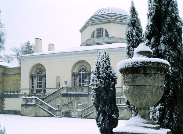 CHISWICK HOUSE AND GARDENS, London. An exterior view of the Palladian style north front of the house with snow covered urn in the foreground