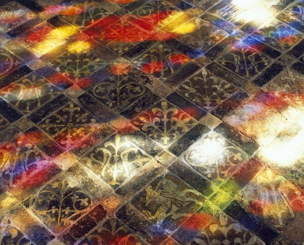CHURCH OF ST PETER AND ST PAUL, Muchelney, Somerset. Interior detail of chancel floor tiles lit by coloured light from stained glass window