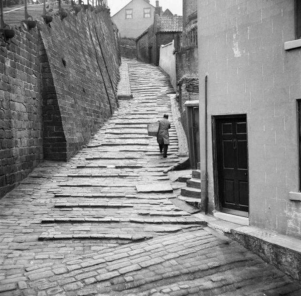 THE CHURCH STAIRS, Whitby, North Yorkshire. A baker makes deliveries, climbing the steps from the quayside to the church. 1950s. Hallam Ashley