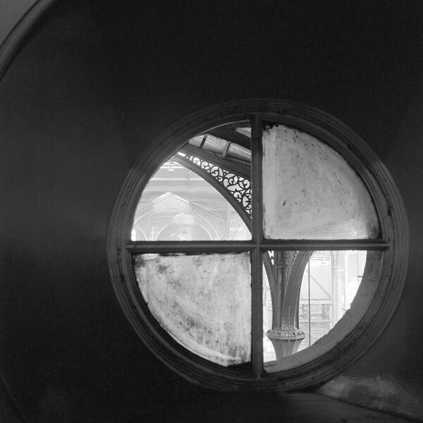 LIVERPOOL STREET STATION, London. Interior view through a small circular window towards ornate cast iron spandrels supporting the roof structure at Liverpool Street Station. Photographed by John Gay. Date range: 1960-1972