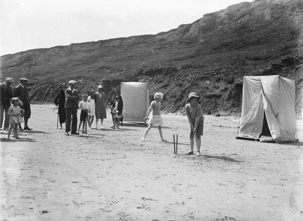Filey, North Yorkshire. Children playing cricket on the beach, with two bathing tents in the background. Photographed for the Walter Scott postcard company in 1930
