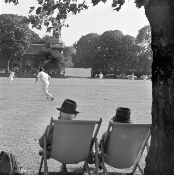 KEW GREEN, London. Rear view of an elderly couple seated on deckchairs watching a cricket match being played on Kew Green. John Gay. Date range: Jan 1962 - May 1964