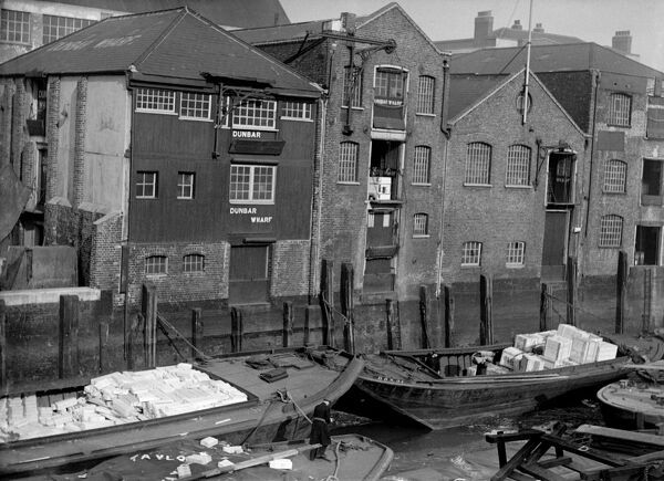 DUNBAR WHARF, Narrow Street, Limehouse, London. This Thames-side wharf was built in the early 19th century for Duncan Dunbar & Sons. Lighters with cargo are moored against the wharf, and cranes raise goods to the warehouse doorways above. Photographed by S