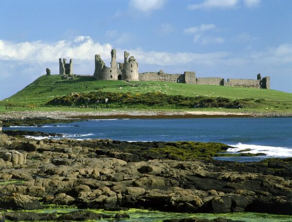 DUNSTANBURGH CASTLE, Northumberland. View of the castle with rocks and sea in the foreground