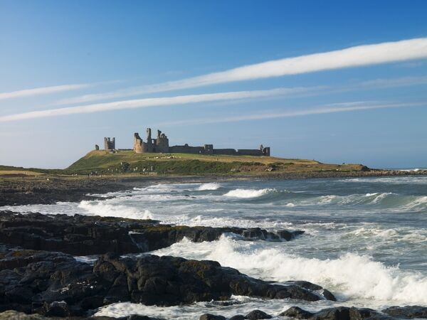 DUNSTANBURGH CASTLE, Northumberland. The castle from the shoreline with waves crashing on to the rocks