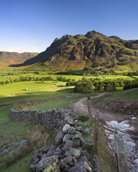 LANGDALE PIKES, Lake District National Park, Langdale, Cumbria. Mountain in the morning sunlight with footpath and wall