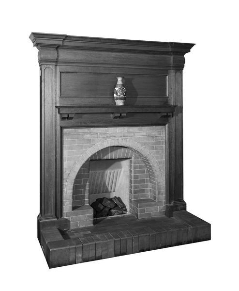Detail of a tiled fireplace with wooden surround from the showrooms of the Well Fire Company in 33 Dover Street, Mayfair, London. The photograph was taken in the showrooms of The Well Fire Co. Ltd., who are recorded as clients for this image