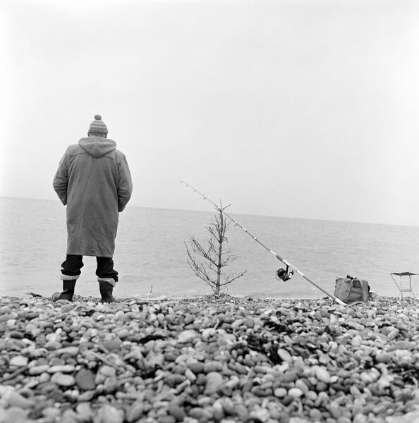A man fishing on a shingle beach in Kent, with his fishing rod propped on a bare Christmas tree. Photographed by John Gay. Date range: 1965 - 1972