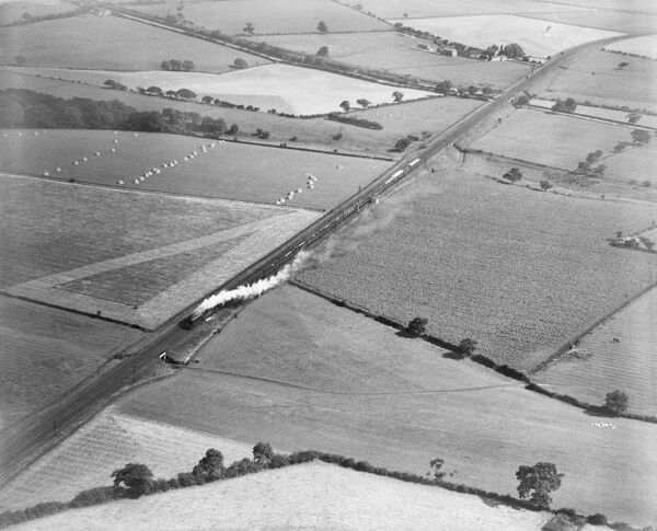 "An LNER A1 ""Pacific"" class locomotive hauling the ""Flying Scotsman"" towards Edinburgh. Red House, Framwellgate Moor, County Durham. Photographed by Aerofilms Ltd in 1926"
