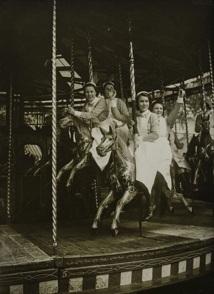 Soho Square Gardens, Westminster, Greater London. Nurses waving from the merry-go-round at The Soho Fair and Market. Photographed for the Topical Press Agency Ltd in July 1939