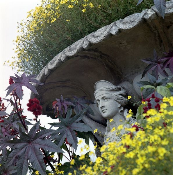 OSBORNE HOUSE, Isle of Wight. Detail of garden sculpture. Face on a giant urn planted with flowers