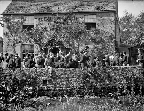 GEORGE INN, Botley, Oxfordshire. View from Seacourt Stream showing a group outside the George Inn, Beating the Bounds - a traditional ceremony which evolved during the reign of Elizabeth I, and involves beating the parish boundary stones with