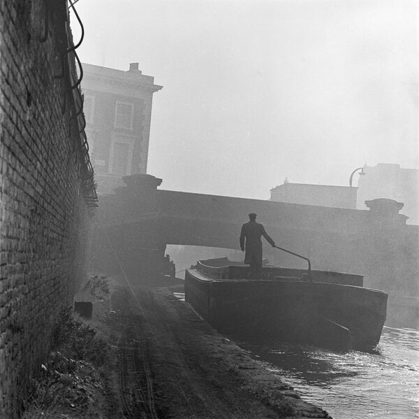 GRAND UNION CANAL, London. A view from a misty canal towpath showing a man steering an industrial canal barge along the canal towards a road bridge. Photograph 1955-1965, John Gay