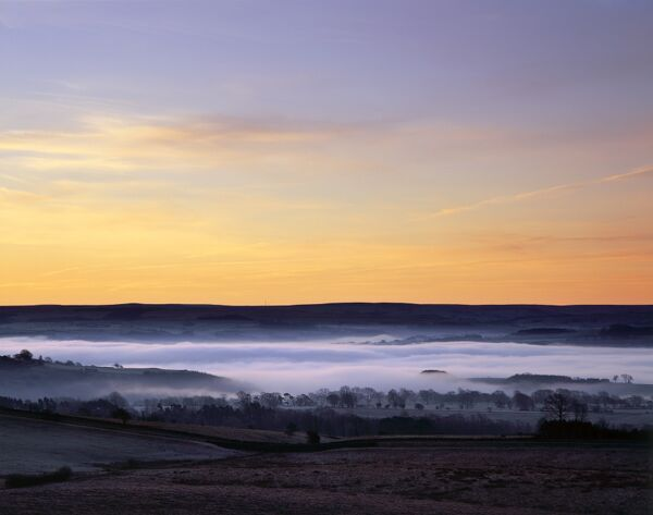 HADRIAN'S WALL, Northumberland. View from Peel Crags, near turret 39A. Mist fills the valley south of the wall at day-break as the sky reflects the pre-dawn light. hadrian
