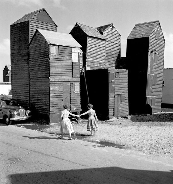 HASTINGS, East Sussex. View of two women walking past a group of fishermen's stores ('net shops') during 1956. Eric de Mare