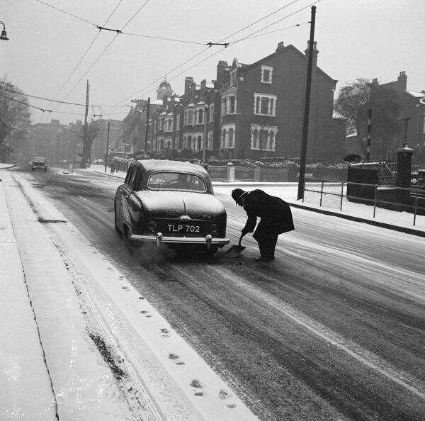 Highgate Hill, Greater London. A policeman shovelling grit under the wheel of car that is stuck on a snowy road. Photographed by John Gay, 1950s-60s